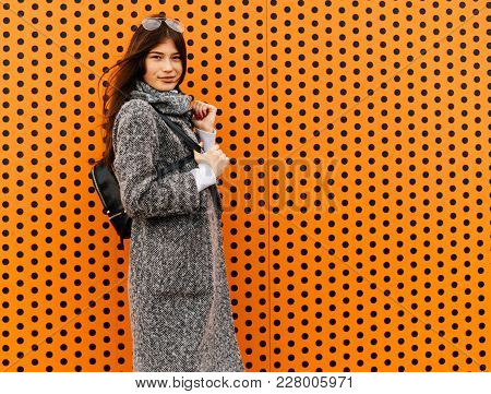 Stylish Cute Girl In A Trendy Gray Coat Posing Against An Unusual Orange Wall, Street Style