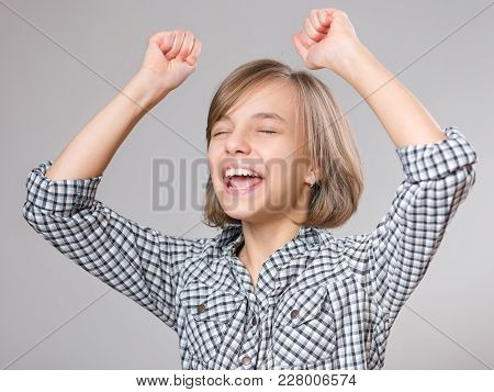Close-up Emotional Portrait Of Caucasian Little Girl. Funny Victory Screaming Teenager, On Gray Back