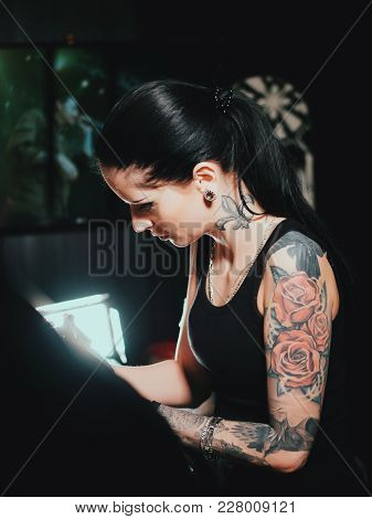 Close Up Of Artist Demonstrates The Process Of Getting Black Tattoo With Paint. Master Working In Wo
