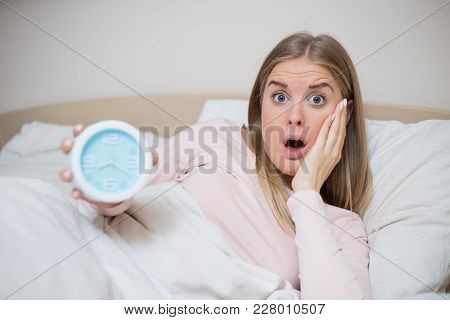 Image Of Terrified Woman Holding Alarm Clock.