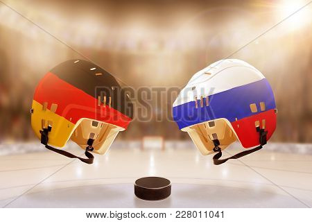 Low Angle View Of Hockey Helmets With Painted Germany And Russia Flags, And Hockey Puck On Ice In Br