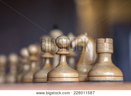 Close Up View Of White Chess Pieces Lined Up On A Chess Board Ready For A Game With Selective Focus