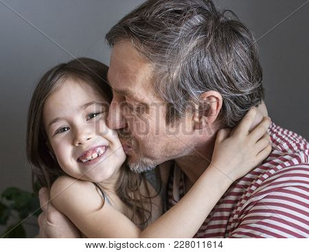 Grandfather Kisses His Beloved Granddaughter, Holding Her In His Arms