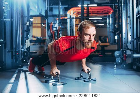 Serious Fit Black African American Man Performing A Pushup From Light Wooden Floor Against A White W
