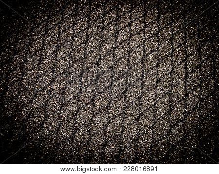 Shadow From Mesh Fencing On Asphalt With Dark Frame