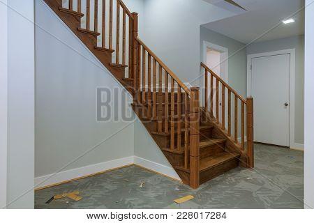 Hallway Interior With Hardwood Floor. View Of Wooden Stairs. Door Beside The Stairs