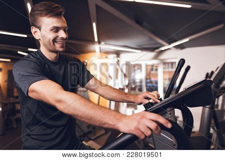A Man Is Doing Sports In The Gym. He Leads A Healthy Lifestyle. A Man Is Engaged In An Elliptical Tr