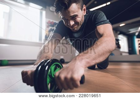 A Man Is Doing Sports In The Gym. He Leads A Healthy Lifestyle. Man Is Engaged On The Simulator In T