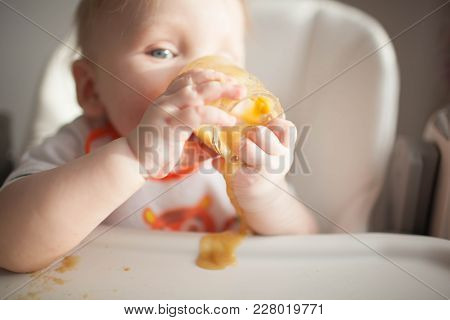 Baby 6 Months Old And He For The First Time Tries Vegetable Squash. Spoon For Feeding