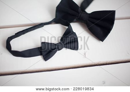 Black Bow Tie Isolated On White Background. Wooden White Background