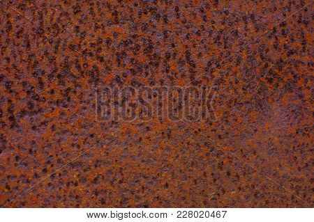 Rusty Yellow-red Textured Metal Surface. The Texture Of The Metal Sheet Is Prone To Oxidation And Co