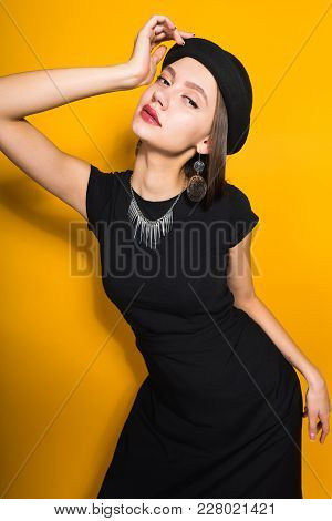 Beautiful Attractive Model Girl In Fashionable Black Hat Posing On Yellow Background, Expensive Jewe