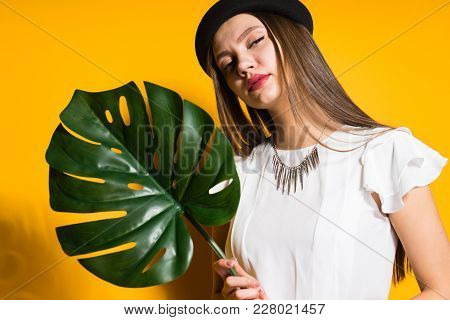 Attractive Young Girl Model In A Trendy Black Hat Holds A Green Leaf And Poses