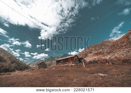 Unfinished Lonely Forsaken Wooden House Surrounded By Hills With Meadow In Foreground; Abandoned Dil