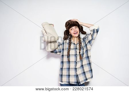 Happy Smiling Russian Girl In A Warm Hat With Ear-flaps Holds Gray Felt Boots