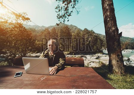 Aged Grey Haired Hunter Is Sitting At Big Wooden Table And Checking His E-mail Via Laptop; Mature Ma