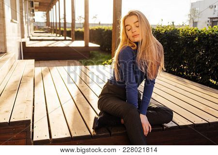 Attractive Young Blond Model Girl In Stylish Blue Sweater Posing In The Sun In The Open Air