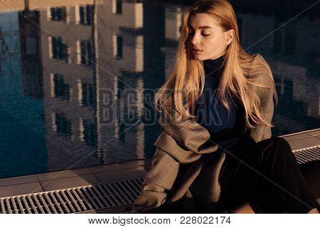Attractive Young Blonde Girl In Stylish Clothes Posing By The Pool In The Sun
