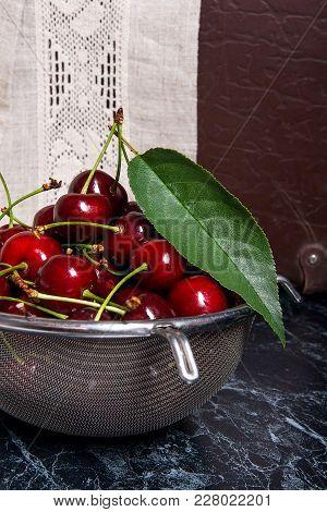 Fresh Organic Sweet Cherry In Steel Colander On Dark Marble Background..