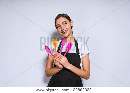 Happy Young Girl Cook In Black Apron Holds In Hands Cooking Tools