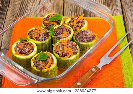 Vegetarian Dish. Raw Zucchini Stuffed With Red Rice With Vegetables. Studio Photo