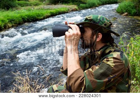 The Naturalist In Military Uniform With Binoculars Is On Bird Watching Mission In Nature At Riversid