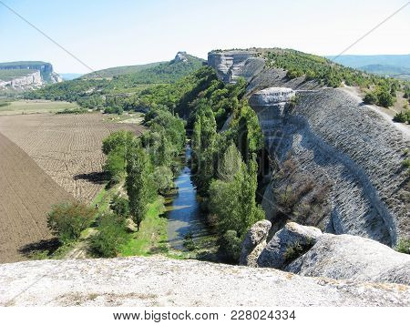 High Smooth Light Stone Ridge At The Foot Of Which Flows A Small Narrow River Surrounded By Tall Gre
