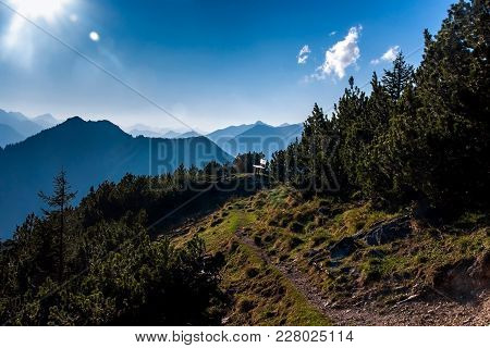 Small Stony Walkway On The Mountain In The Alps With Bench At The End