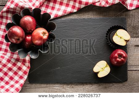 Ripe Red Apples On Wooden Board With Red Checkered Towel Around And Accessories For Baking. Copy Spa