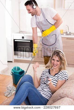Man Mopping Floor While Woman Resting On Sofa