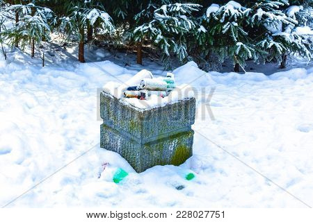 Snow-covered Urn For Garbage In The Winter Park. Pull In The Snow With Spruces On Background