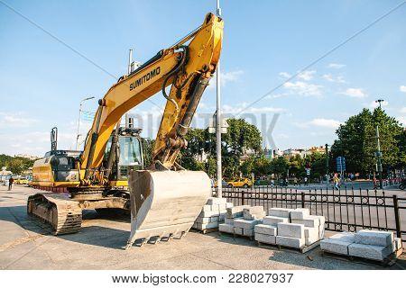 Istanbul, June 15, 2017: Yellow Industrial Sumitomo Excavator Next To Stacks Of Quarry Brick
