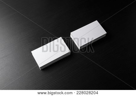 Photo Of Blank Business Cards Stacks On Black Wood Table Background. Template For Branding Identity.