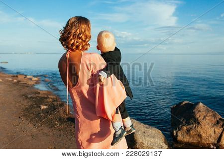 Back view of young mother and her cute baby boy, dressed for a festive event is standing on the beach admiring the blue sea on beautiful summer day. Happy family concept