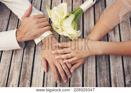 The Top View Of The Hands With The Engagement Rings Of The Bride And Groom, And A Bouquet Of White C