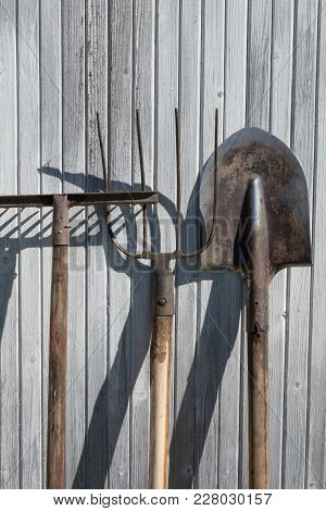 The Old Rusty Tools, Implements Or Household Equipment On Wooden Vintage Background.