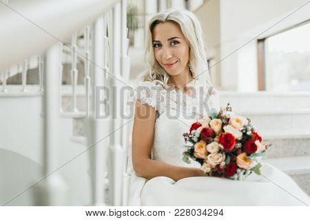 Beautiful Cheerful Bride With A Bouquet Sits On The Stairs. Wedding Morning. Copy Space Indoor