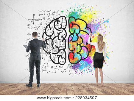 Rear View Of A Businessman And A Businesswoman Drawing A Colorful Large Brain Sketch On A Concrete W
