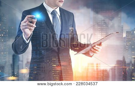 Unrecognizable Young Businessman Is Looking At His Clipboard And Holding A Glowing Marker. A Citysca
