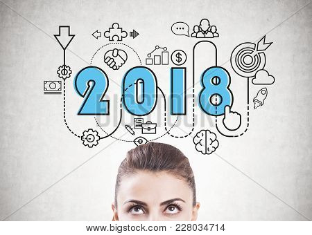 Portrait Of An Attractive Young Brunette Woman Looking Upwards At A Bright 2018 Business Plan Sketch
