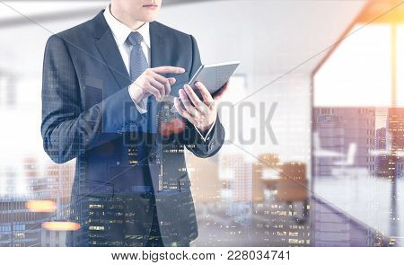 Unrecognizable Young Businessman Wearing A Dark Suit With A Tie And Working With A Digital Tablet In