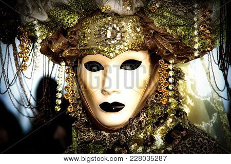Costumed Reveler Of The Carnival Of Venice In A Green And Yellow Costume And A Black Vignette.