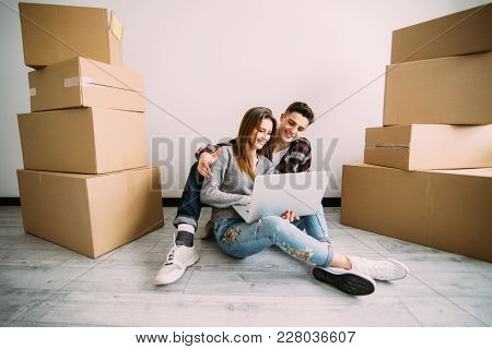 Young Couple In Love Sitting On The Floor Of Their New Apartment, Planning Redecoration And Searchin