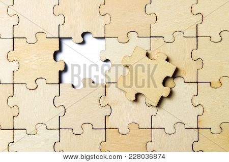 Finishing The Last Piece Of A Jigsaw Wooden Puzzle Game On White