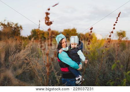 Tender Woman In Turquoise Hat Standing At Dry High Grass Background Hugging Little Cute Child Baby B