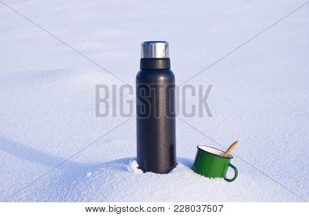 Thermos And Mug In The Snow. Nature Composition