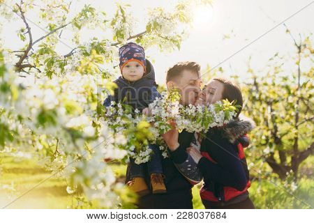 Joyful Man, Woman Rest On Nature Hug, Play, Kiss With Little Cute Child Baby Boy. Mother, Father, Li