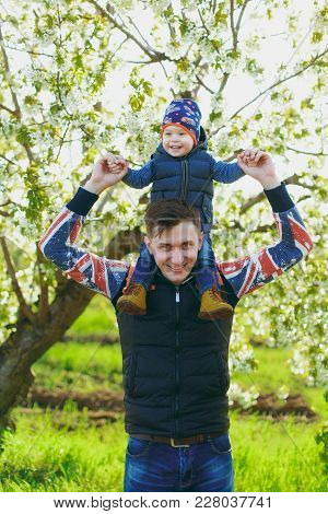 Smiling Fun Man Rest On Nature Hug, Play, Kiss With Little Cute Child Baby Boy. Father Keeps On Shou