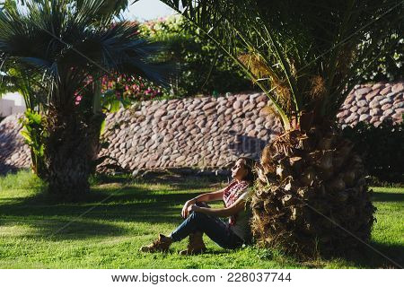 Girl Sitting On The Grass Under A Palm Tree At Sunset. Summer Sunny Day In Egypt. Concept Of Tourism