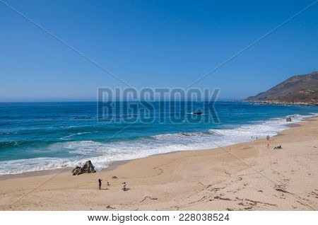Parents And Children Playing And Taking Pictures At The Beach On The Pacific Ocean